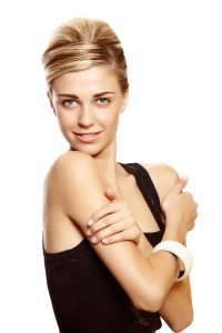 Beautiful blond woman with natural make-up wearing hair in a classic french roll updo hairstyle over white studio background .