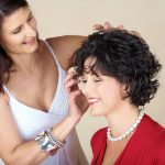 Happy woman in her 40s styling short hair curls on her friend